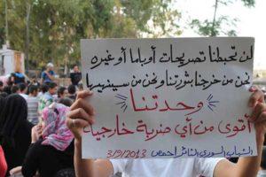 """Protest w kontrolowanym przez rebeliantów mieście Homs.  Napis: """"Rozpoczęliśmy naszą rewolucję i ją zakończymy. Nasza jedność jest silniejsza od jakiegokolwiek obcego nalotu."""""""