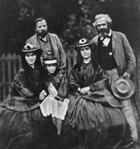 Rok 1864. Eleonora Marks siedząca między swoimi siostrami Laurą i Jenny. Za nimi stoją Fryderyk Engels i Karol Marks.